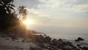Amazing sunset over tropical island beach and palm trees, Koh Samui. Thailand. Waves hit the stones in slow motion. Sunset over tropical island beach and palm stock footage