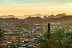 Sunset over Tucson, Arizona USA. Sunset over Tucson suburbs, Arizona, showing mountains and saguaro cactus, warm yellow sunlight Stock Photos