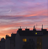 Sunset over urban rooftops. With lights from some home windows Royalty Free Stock Images
