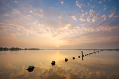 Sunset over Valkenburgse Meer. A tranquil sunset over a mirroring lake Stock Photos