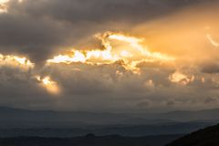 Sunset over a valley with sun rays coming out through some clouds. Sunset over a valley, with sun rays coming out through some clouds Royalty Free Stock Photos