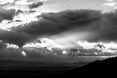Sunset over a valley, with sun rays coming out through some clouds Stock Photos