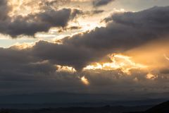 Sunset over a valley with sun rays coming out through some clouds. Sunset over a valley, with sun rays coming out through some clouds Royalty Free Stock Photo