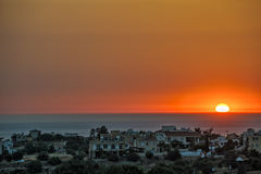 Sunset over village on sea coast Stock Photo