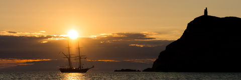 Sunset over vintage tall ship beside headland in Port Erin in the Isle of Man Stock Images