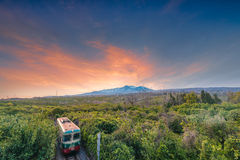 Sunset over Volcano Etna seen from Giarre. Landscape over Giarre countryside, with Volcano Etna in the background. In the foreground, one of the old trains of Royalty Free Stock Photos