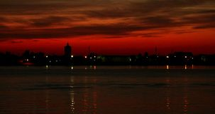 Sunset over Volga-river In Astrakhan with beautiful red sky, timelapse DCI4K. Summer sunset cityscape panorama timelapse stock video