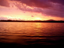Sunset Over Water. A fiery sunset over calm water Royalty Free Stock Photo