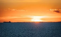 Sunset over water with cargo ship and clouds stock photo