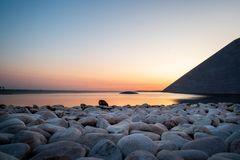 Sunset over a water font and some rocks with the sea on the back. Ground and a orange sky Stock Photo