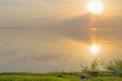Sunset over water lake coast water summer Stock Image