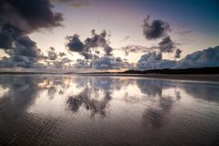 Sunset over waterfront, Donegal, Ireland. Sunset through clouds reflecting in calm waters off beach in Donegal, Ireland Stock Image