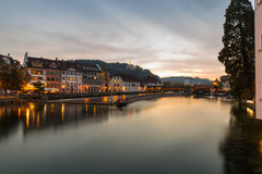 Sunset over the waterfront, Lucerne , Switzerland. With the orange glow of the sky and lights in the buildings reflected in the calm water of the lake in a Stock Photos