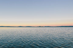 Sunset over waters along coastline Royalty Free Stock Photography