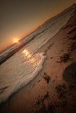 Sunset over waves on beach. Angled view of orange sunset over waves breaking on sandy beach Stock Photos