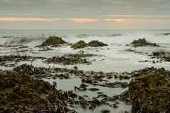 Sunset over waves and rocks Stock Photo