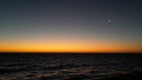 Sunset with tiny moon royalty free stock photo