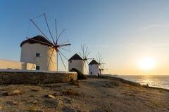 Sunset over White windmills on the island of Mykonos, Greece Stock Photo