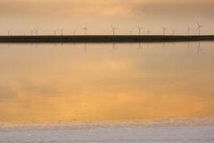 Sunset over the wind farm with reflection on lake Stock Photography