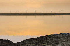 Sunset over the wind farm with reflection on lake Stock Images