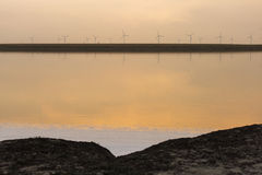Sunset over the wind farm with reflection on lake Stock Image