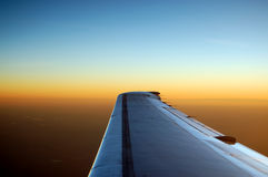 Sunset over the Wing. A wing of an airplane over a sunset horizon Royalty Free Stock Images