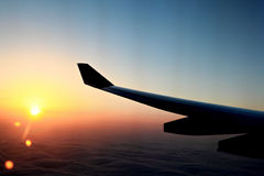 Sunset over the wing in airplane Royalty Free Stock Photography