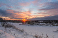Sunset over the winter field. Winter landscape forest types of fields and sky Royalty Free Stock Photography