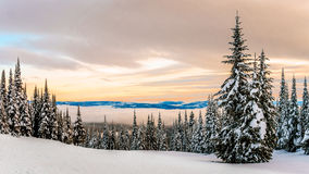 Sunset over the Winter Landscape with Snow Covered Trees on the Ski Hills Stock Photos
