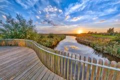 Sunset over Wooden Balustrade  on bridge Stock Photo