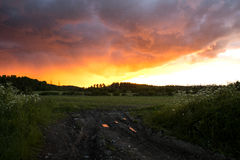 Sunset over the Worndown Dirt Road through the Field Royalty Free Stock Image