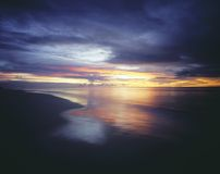 Sunset and Overcast Sky Over Beach Royalty Free Stock Photos
