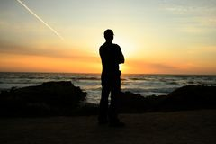 Sunset on the Pacific. Man watching the sun set over the Pacific Ocean Stock Photography