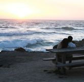 Sunset on the Pacific. Couple watching the sun set over the Pacific Ocean Royalty Free Stock Photography