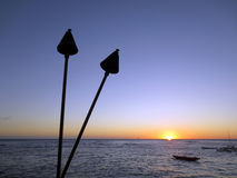 Sunset on Pacific Ocean with tiki torches and canoes Royalty Free Stock Image
