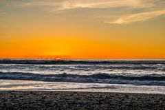 Sunset through the pacific surf. Top of the waves are being blow off in front of the sun. Royalty Free Stock Photos