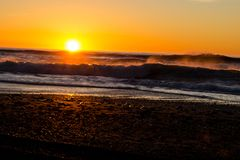 Sunset through the pacific surf. Top of the waves are being blow off in front of the sun. Stock Photos