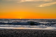 Sunset through the pacific surf. Top of the waves are being blow off in front of the sun. Stock Images