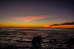 Sunset through the pacific surf. Top of the waves are being blow off in front of the sun. Royalty Free Stock Images