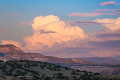 Free Sunset Paints Cumulus Clouds And Thunderheads In Soft Colors Of Pink, Purple And Peach Over A Colorful Desert Landscape Stock Photography - 150854982