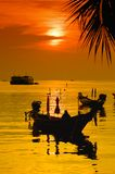 Sunset with palm and boats on tropical beach. Sunset with palm and longtail boats on tropical beach. Ko Tao island, Thailand Royalty Free Stock Photo