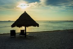 Sunset between palm trees and beach umbrellas at Thailand stock images