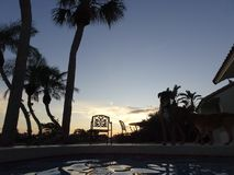 Sunset and palm trees at the swimming pool. Tropical sunset at the swimming pool Stock Images
