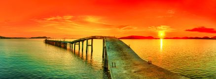 Sunset panorama. Sunset over the sea. Pier on the foreground. Panorama Stock Photo