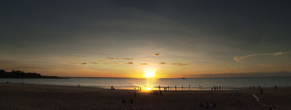 Sunset panorama over the beach. Sunsetting over the ocean with people playing on the beach Royalty Free Stock Images