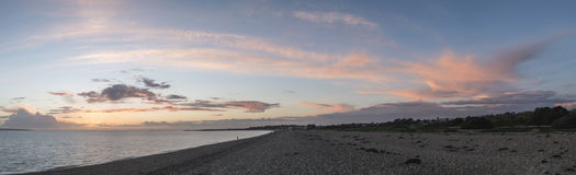Sunset panorama over shingle beach with colorful vibrant sky and Royalty Free Stock Photography