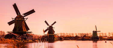 Sunset panorama with windmills in Zaanse Schans, Holland. Sunset panoramic banner with windmills and lake in Zaanse Schans, traditional village in Holland, copy royalty free stock images