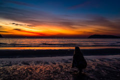 Sunset in Pantai Tengah beach, Langkawi, Malaysia. Girl looking a the last traces of light in the sky Stock Image