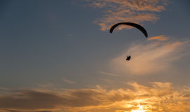 Sunset para gliding. A silhouetted para glider soars towards the setting sun Royalty Free Stock Photo