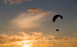 Sunset para gliding. A silhouetted para gliders soar towards the setting sun Royalty Free Stock Photos